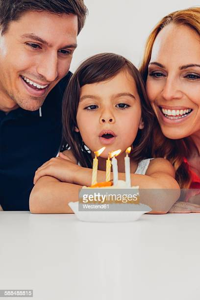 Family with daughter celebrating birthday with candles on cake