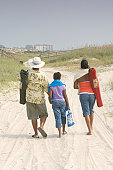 Family with daughter (10-11years) walks between sand dunes, rear view
