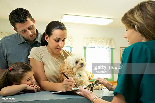 Family with dog filling out paperwork at vet clinic