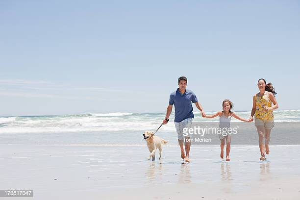 Family with dog running on beach