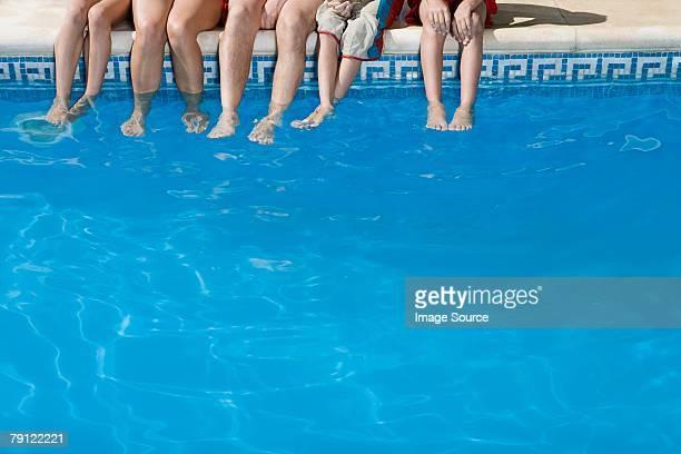 Famille avec les pieds dans la piscine