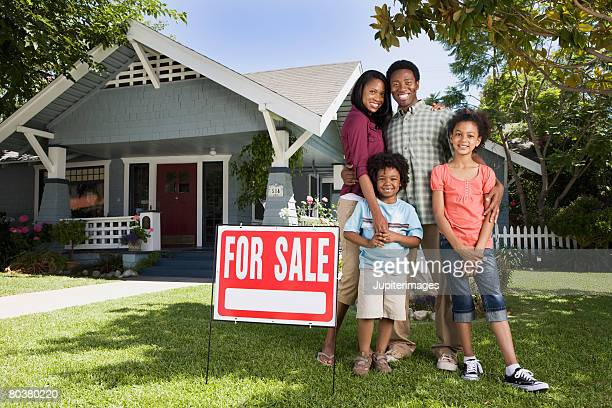 Family with For Sale sign in front of house