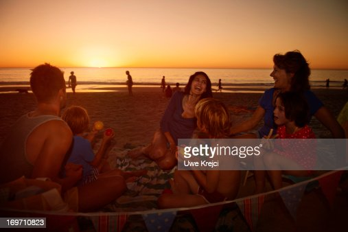 Family with grandmother relaxing on beach : Stock Photo