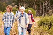 Family with grandmother walking through a forest together