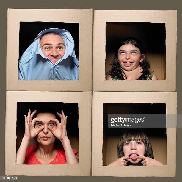 Famille avec têtes dans des boîtes tirant des visages