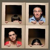 Familie mit Köpfen in Schachteln ziehen Gesichter