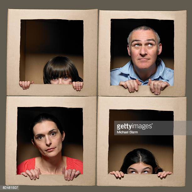 Family with heads in boxes pulling faces