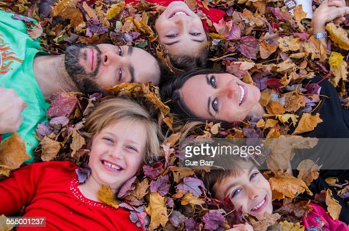 Family with heads together, lying in autumn leaves