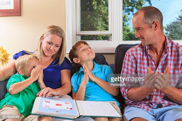 Family with hearing impairments looking at a photo album and signing book in American sign language on their couch