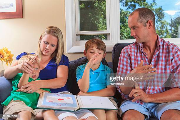 Family with hearing impairments looking at a photo album and signing flag in American sign language on their couch