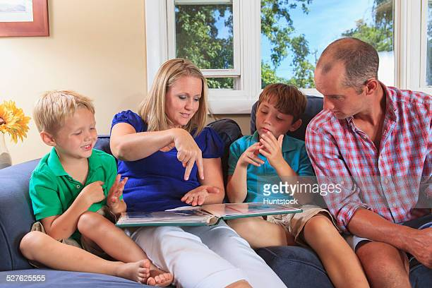 Family with hearing impairments looking at a photo album and signing jump in American sign language on their couch