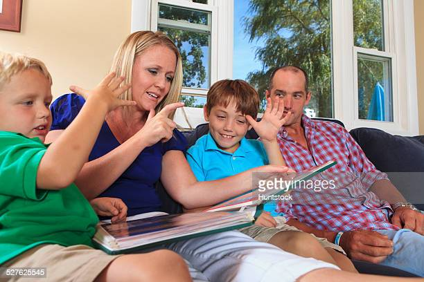 Family with hearing impairments watching photo album and signing who, Daddy in American sign language on their couch
