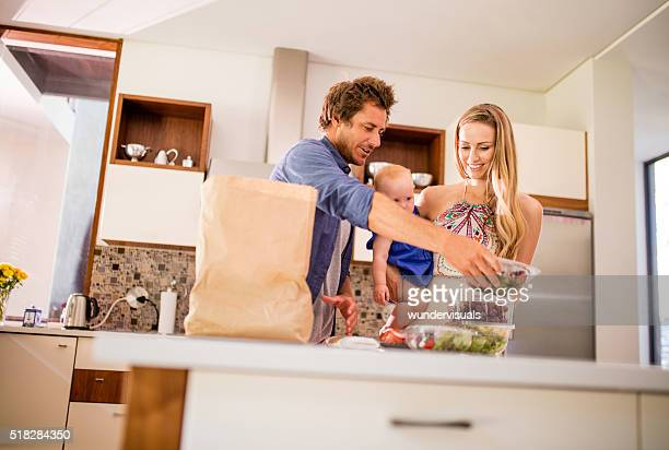 Family with Infant Daughter Unpacking Groceries in Kitchen
