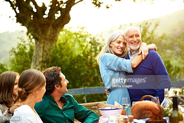 Family with loving couple having meal in yard