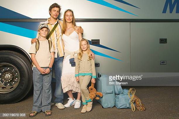 Family with luggage beside bus, portrait