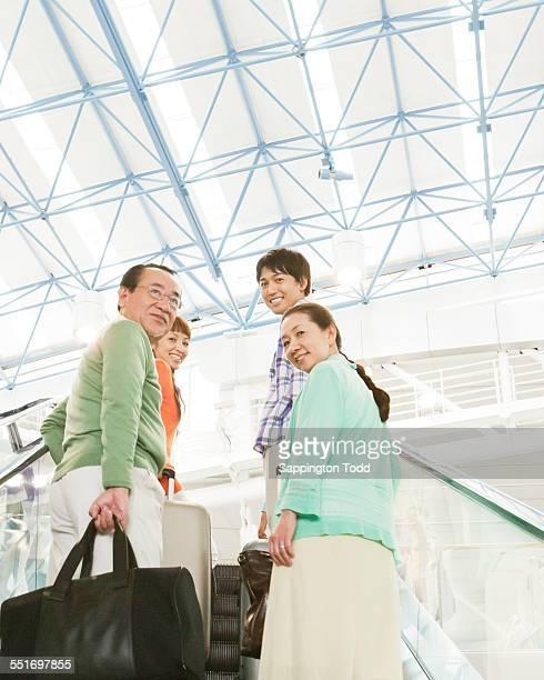 Family With Luggage On Escalator