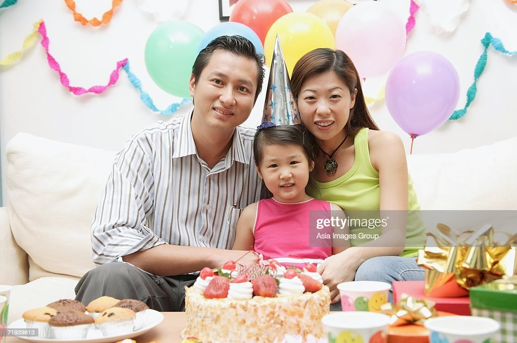 Family with one child sitting with birthday cake, portrait : Stock Photo