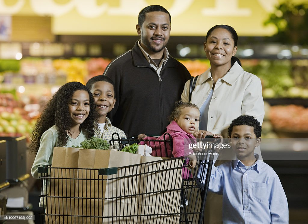 Family with shopping trolley in supermarket, smiling, portrait : Stock Photo