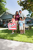 Family with sold sign in front of house