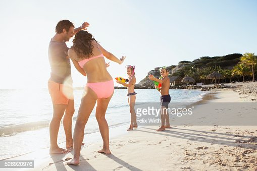Family with son (8-9) and daughter (10-11) playing on beach : Stock Photo