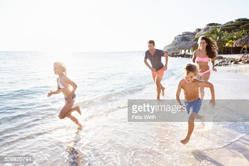 Family with son (8-9) and daughter (10-11) running on beach : Stockfoto