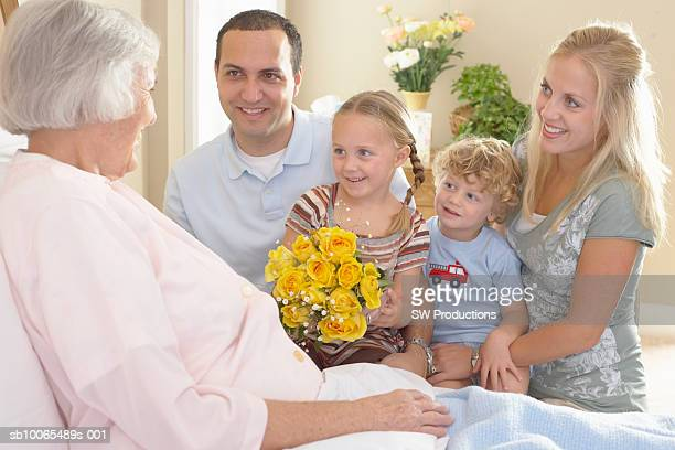 Family with son (2-3 years) and daughter (3-4 years) visiting elderly woman in hospital