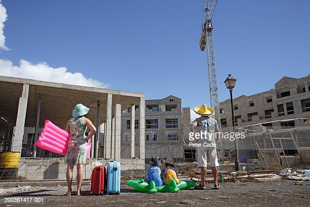 Family with suitcases facing building under construction, rear view