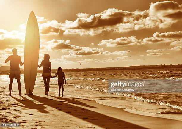 Familie mit Surfbrett am Strand