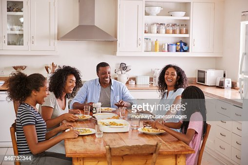 Family With Teenage Children Eating Meal In Kitchen : Stock Photo