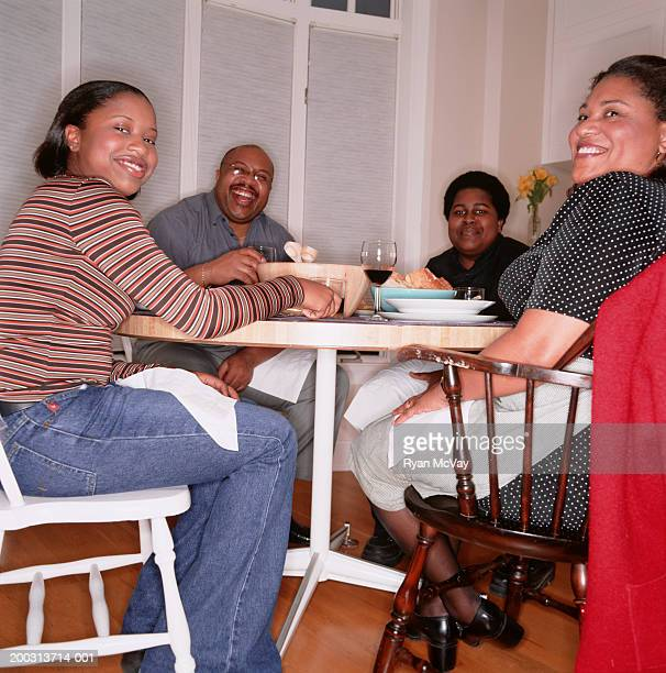 Family with teenage son and daughter (16-17), sitting at kitchen table, portrait