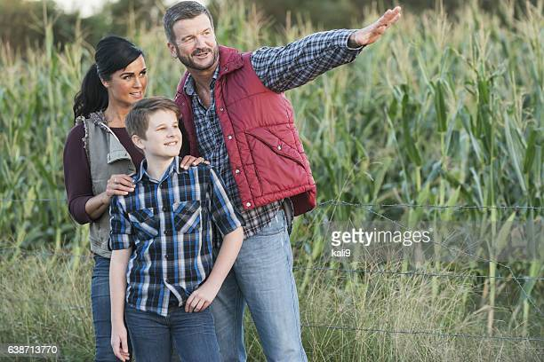 Family with teenage son on a farm by corn field