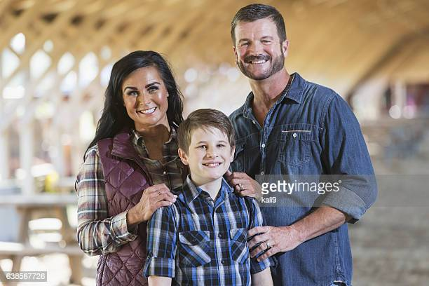 Family with teenage son on farm in barn