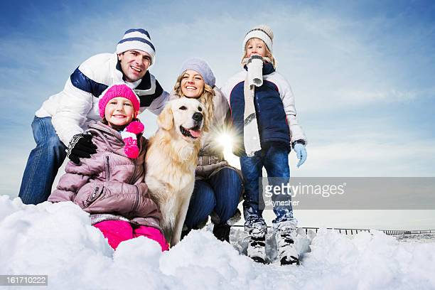 Family with their dog enjoying in the snow.