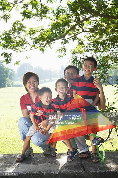 Family with three boys, outdoors, smiling at camera