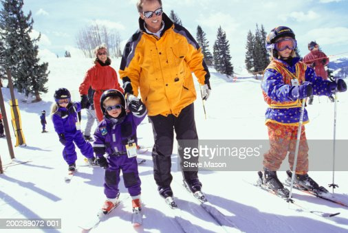Family with three children (4--7 skiing
