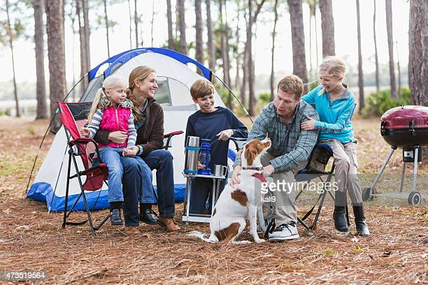 Family with three children and dog on a camping trip