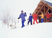 Family with three children (10-11), (13-14), (14-15) and dog snowshoeing in mountains, low angle view