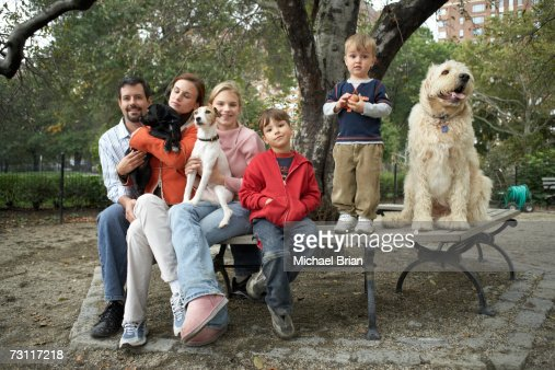 Family with three children (4-13) and dogs sitting on bench in park, portrait : Stock Photo