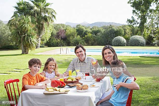 Family with three children (6-11) sitting at table in garden portrait