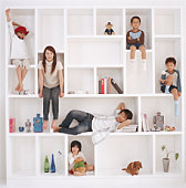 Family with three children (4-9) sitting in cabinet of book shelf