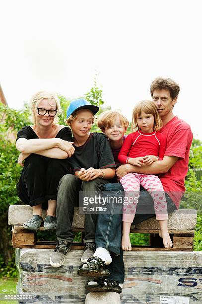 Family with three children sitting in park
