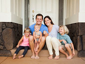 Family with three kids (6-7, 2-3, 6-11 months) sitting in front of house