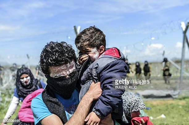 TOPSHOT A family with toothpaste smeared over their faces as a protection against teargas moves to safety as refugees and migrants clash with...