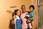 Family with toy house and paint roller