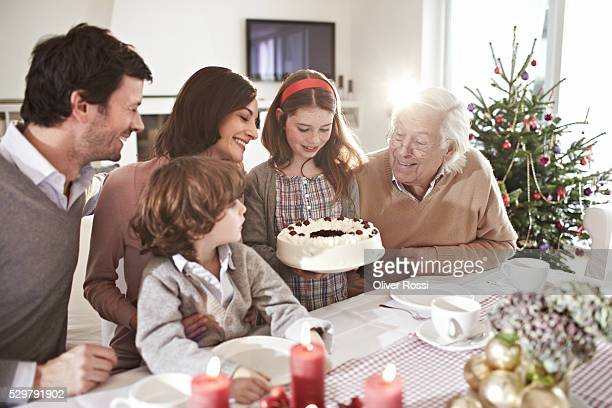 Family with two children (7-9) admiring cake at Christmas table