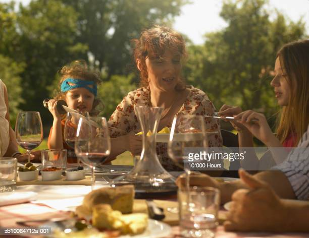 Family with two children (5-11) dining outdoors