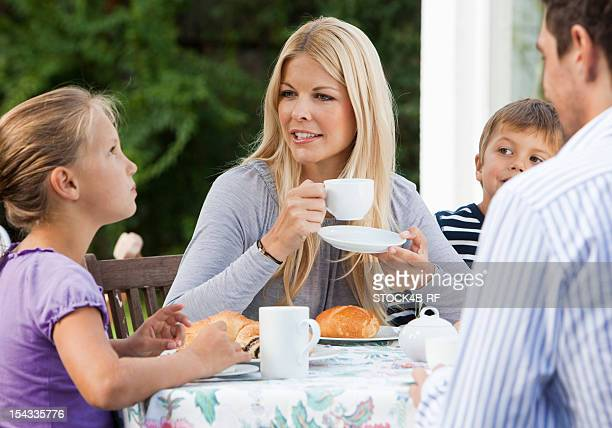 Family with two children having breakfast on terrace