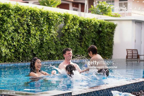 family with two children having fun at swimming pool