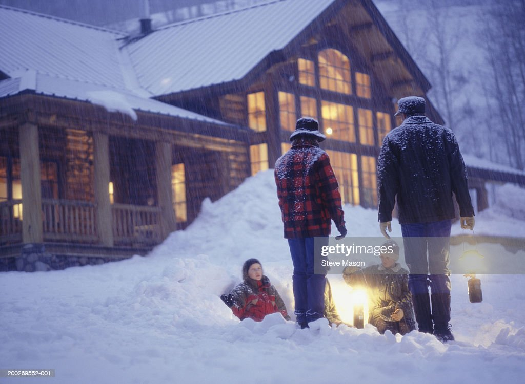 Family with two children (10-11), (12-13) in snow, holding lanterns