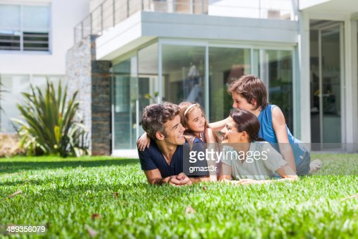 Family with two children lying on grass : Stock Photo